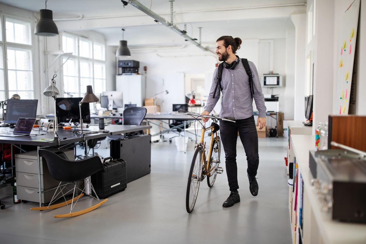 Mitarbeiter schiebt sein Fahrrad zum Feierabend durch das Büro