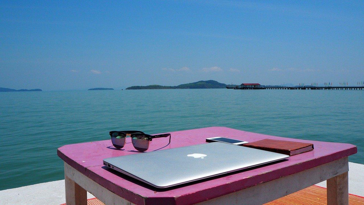 MacBook auf einer Ablage vor dem Meer als Symbol für freies Arbeiten von überall